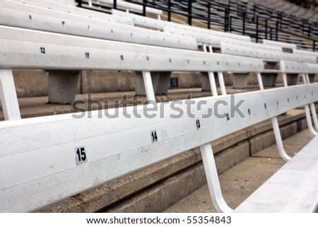 A picture of some empty bleacher seating in rows, taken in a modern school sports stadium facility. - stock photo