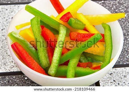 a picture of some sliced yellow green red paprika  - stock photo