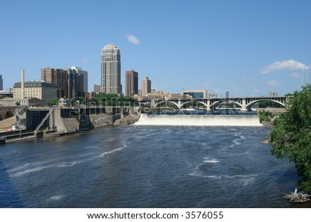 A picture of St. Anthony's Falls next to parts of Minneapolis skyline - stock photo