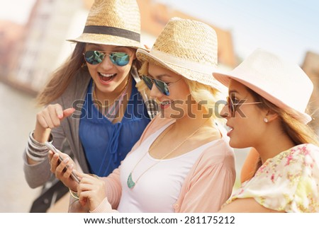 A picture of three friends using smartphone in the city - stock photo