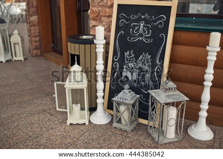 A picture of two wedding cats stand behind white decorative lanterns