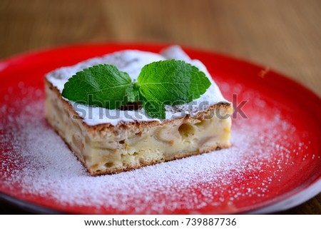 A piece of apple pie, sprinkled with sugar, adorned with a sprig of fresh mint. Served on a red plate, close-up.