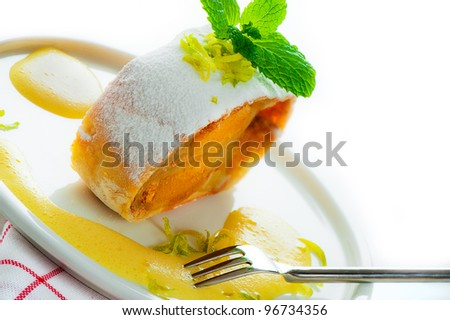 A piece of banana, mango strudel with vanilla sauce and lemon on white background as a studio shot