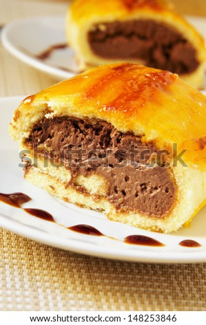 a piece of brazo de gitano, typical spanish swiss roll, filled with chocolate - stock photo