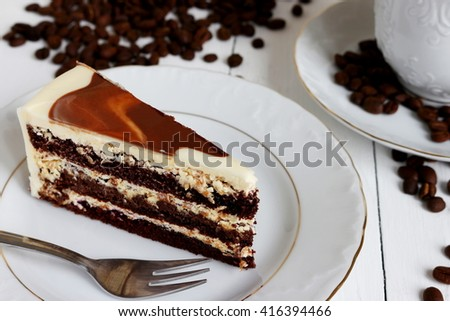 a piece of cake, roasted coffee beans and cup if coffee,   on wooden table painted on white color