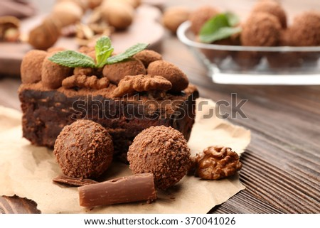 A piece of chocolate cake with walnut and mint on the table, close-up - stock photo