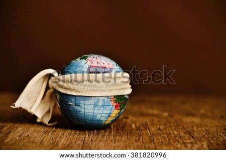 a piece of cloth tied around a terrestrial globe, placed on a rustic wooden surface, with a dramatic effect - stock photo