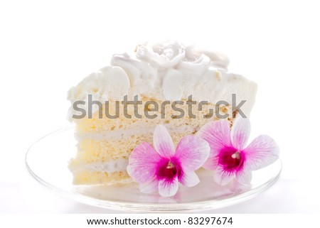A piece of coconut cake with orchids on white background - stock photo