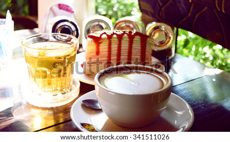 a piece of crepe cake with strawberry sauce and a cup of coffee latte and hot tea on a table - stock photo