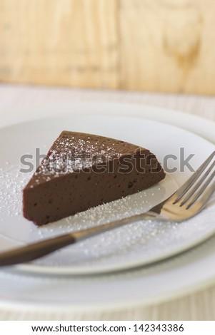 A piece of flourless chocolate cake with powdered sugar. - stock photo