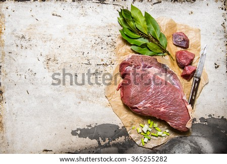 A piece of fresh raw meat with spices . On rustic background. Free space for text . Top view - stock photo
