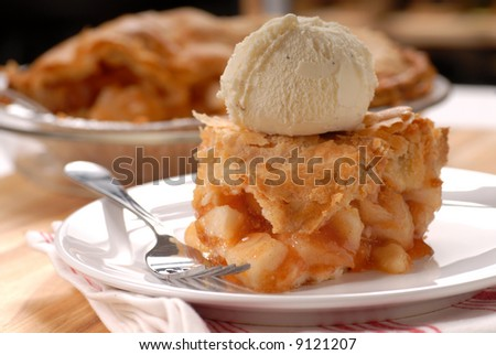 A piece of freshly made deep dish apple pie with a flaky crust and vanilla ice cream