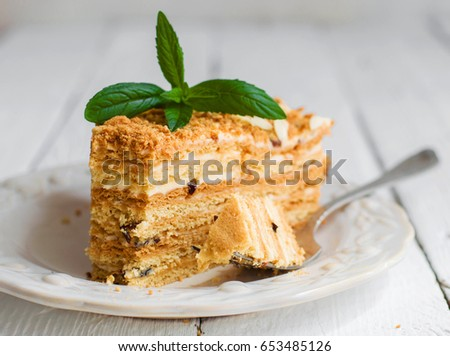 A piece of homemade cake on a white plate and a wooden white background
