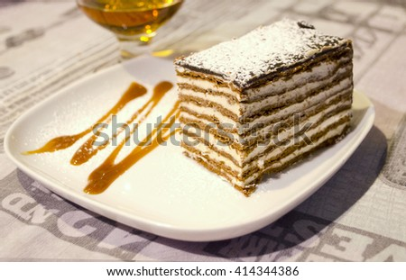A piece of honey cake with custard and chocolate honey shortcakes on decorated plate and glass of brandy on the background. - stock photo