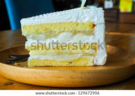 A Piece of layer coconut cake on wooden plate