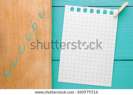 A piece of paper with a pin on turquoise yellow-blue wooden Board
