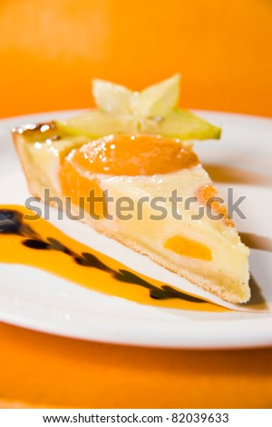 A piece of peach cheesecake on a plate. Orange background. Shallow depth of field.