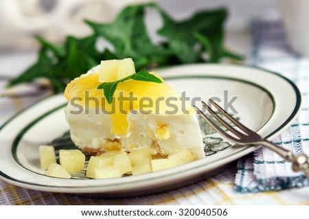 A piece of pineapple cheesecake in a dish - stock photo