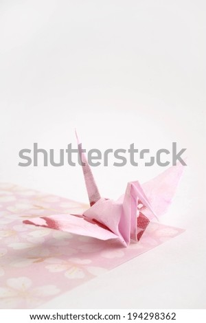 A piece of pink paper folded into origami. - stock photo