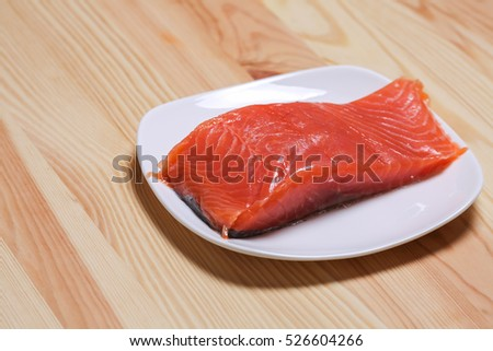 A piece of salmon on a plate lying on a wooden table.