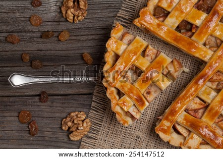 A piece of sliced apple pie with cinnamon and nuts on metal spatula on vintage wooden background texture. Top view - stock photo