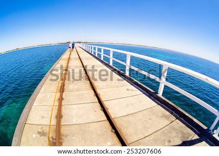 A pier in blue ocean water with fisheye horison in Basselton jetty - stock photo