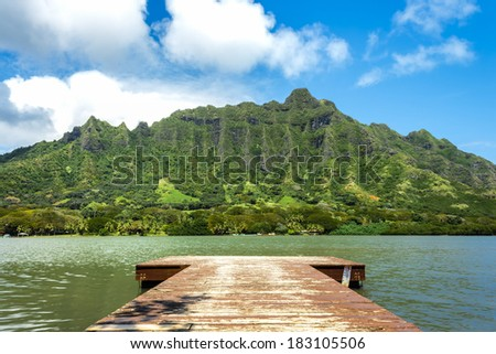 A pier on Molii Fishpond looking toward the Koolau Mountain Range at Kualoa Ranch on Oahu, Hawaii - stock photo