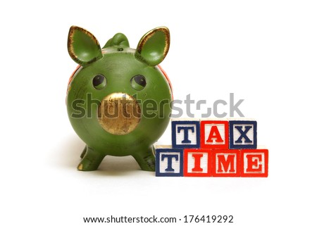 A pig bank and blocks remind people of the tax season. - stock photo