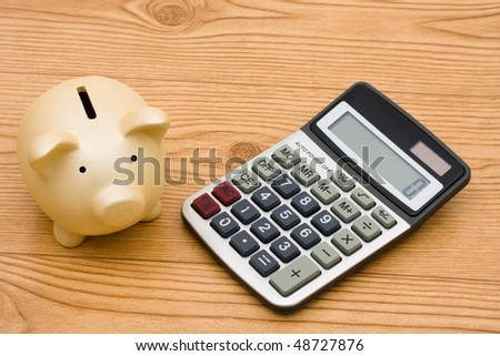 A piggy bank and a calculator sitting on a wooden background, Calculating your expenses