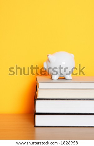 A piggy bank on top of a stack of books, can be used for saving for college design - stock photo