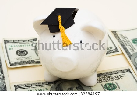 A piggy bank wearing a graduation cap with hundred dollar bills on a beige background, increased education costs - stock photo