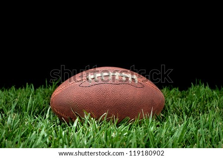 A pigskin football lying in the grass against a black background for placement of copy. - stock photo
