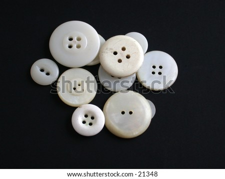 A pile of antique white buttons on a black background - good detail.