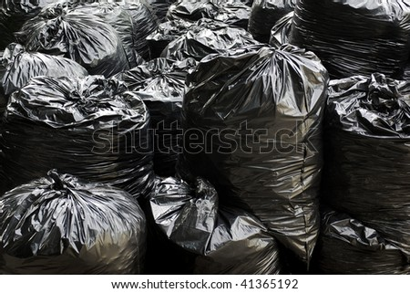 A pile of black garbage plastic bags with tons of trash - stock photo