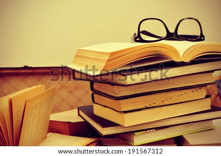 a pile of books and a pair of eyeglasses in an old suitcase, with a retro effect - stock photo