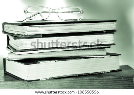 a pile of books and a pair of glasses symbolizing the concept of reading habit or studying - stock photo