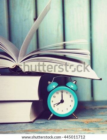 A pile of books and alarm clock. Back to school concept. - stock photo