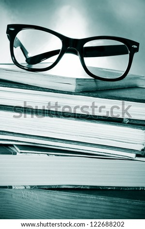 a pile of books and glasses on a desk symbolizing the concept of reading habit or studying - stock photo