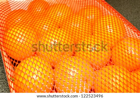 A pile of brightly orange clementines or mandarins under a red plastic mesh for protection during transport. - stock photo