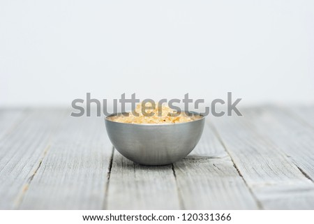 a pile of brown sugar in steel bowl, weathered wooden table background - stock photo