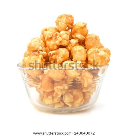 a pile of caramel corn in glass bowl on a white background  - stock photo