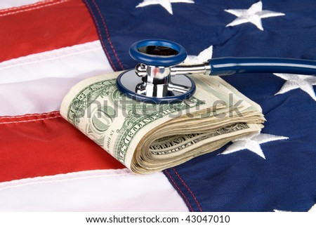 A pile of cash on an American flag with a stethoscope on the money, inferring anything from medical costs to economic health and financial stability. - stock photo