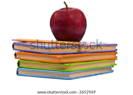A pile of childrens books with a pencil and apple on top. Teachers pet