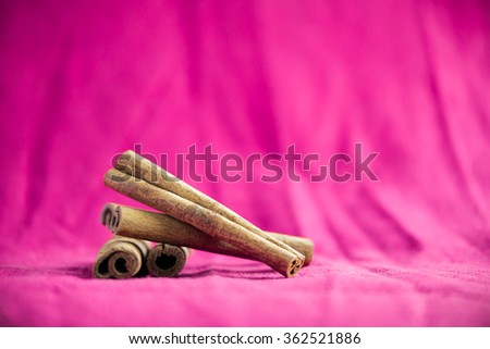 A pile of cinnamon sticks on fuchsia canvas background - stock photo