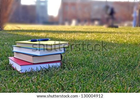 a pile of colorful books on lawn in campus - stock photo