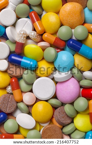 A pile of colorful medications tablets - medical background - stock photo
