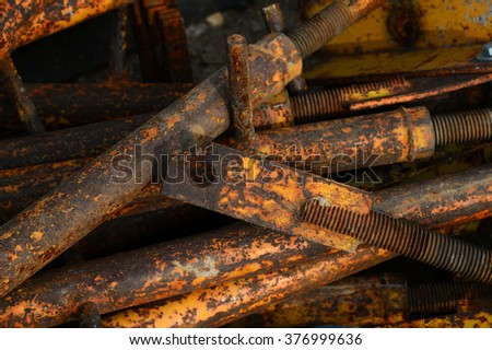 A pile of concrete form ties lies rusting in a contractor's yard. - stock photo
