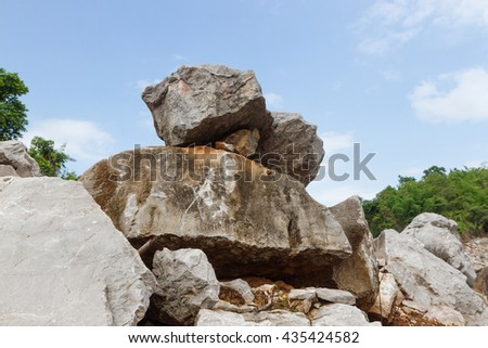 a pile of copper rocks piled up with blue sky and clouds of background