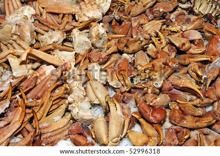 a pile of crabs and crab legs ready to sell in a fish market
