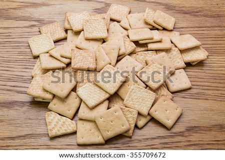 a pile of crackers is on a wooden table - stock photo